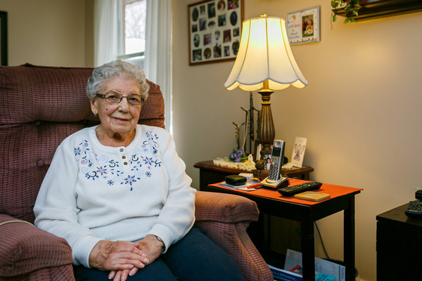 Smiling Elderly Woman Sitting Next to a Lamp